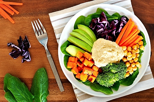 Healthy lunch bowl with avocado, hummus and vegetables